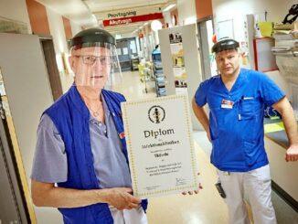 Läkarna Lars Ljungström och Kenny Brandström med diplomet som visar att Infektionsklinikens arbete håller hög kvalitet.